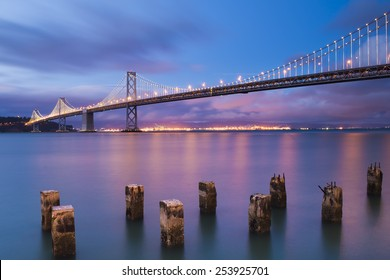 The beautiful San Francisco West Span Bay Bridge at blue hour. Orange glow Oakland Port reflects along water as the pilings silently stand guard. Lights shimmer at Treasure Island in long exposure.
