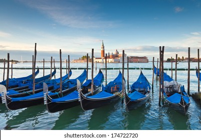 Beautiful San Giorgio Maggiore church, traditional gondolas and street lamps illuminated in the early morning.