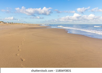 beautiful sandy beach with blue sky clouds, and footsteps forground