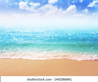 beautiful sandy beach blurred background Sandy shore washing by the wave Bright turquoise ocean water crystal clear sea and bokeh ,summer concept