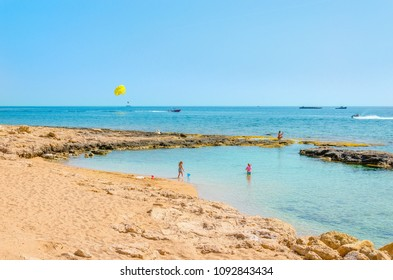 A beautiful sandy beach with children playing and parasailing in the background