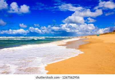 Beautiful sandy beach at the French Atlantic coast side. Sunny summer day with a blue sky and white clouds and powerful waves breaking over a wide empty beach.