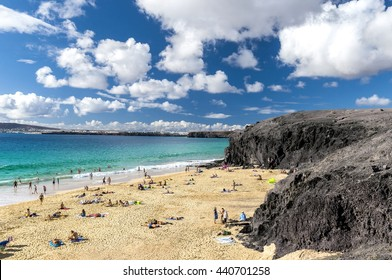 Beautiful sandy beach on the Atlantic Ocean in the village Playa Blanca / A sandy beach surrounded by volcanic mountains. Papagayo beach. Lanzarote. Canary Islands