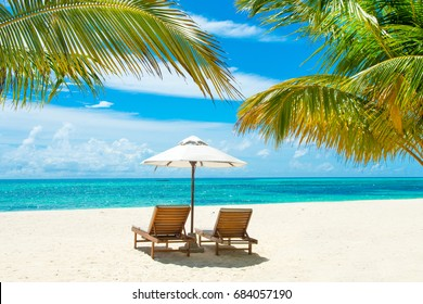 Beautiful sandy beach with sunbeds and umbrellas in Indian ocean, Maldives island