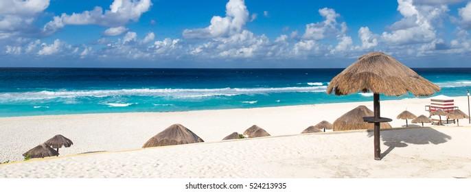 Beautiful sandy beach with thatch parasol