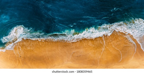 Beautiful sandy beach, top view. Panoramic view of the sandy beach. The sea wave rolls on the shore. Sea coast view from the air. Aerial photography of the sea wave. The ocean and beach. Copy space