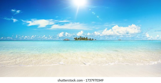 Beautiful sandy beach with white sand and rolling calm wave of turquoise ocean on Sunny day. White clouds in blue sky.  Maldives, perfect scenery landscape, copy space, panoramic view.