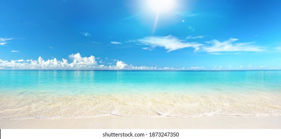 Beautiful sandy beach with white sand and rolling calm wave of turquoise ocean on Sunny day on background white clouds in blue sky. Island in Maldives, colorful perfect panoramic natural landscape. - Shutterstock ID 1873247350