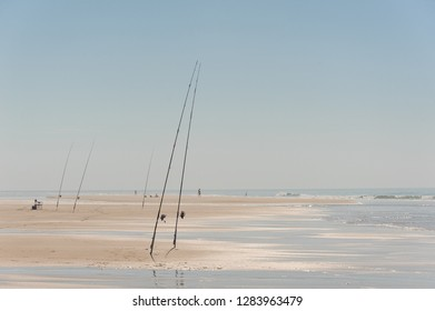 Beautiful sandy sea shore with fishing rods and fishman having a rest near water under the blue sky