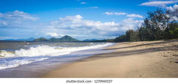 Beautiful sandy tropical beach lined with palm trees in Palm Cove, Cairns, Queensland, Australia