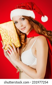 Beautiful santa claus woman wearing christmas hat with golden gift box on red background