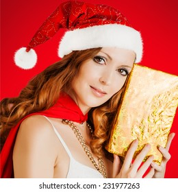 Beautiful santa claus woman wearing christmas hat with golden gift box on white background, studio shot