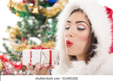 Beautiful Santa girl blowing snow off the silver Christmas gift box in her hand.