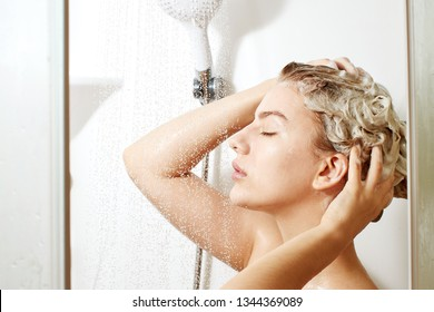Beautiful satisfied European woman washes away shampoo from the head hair in bathroom, takes a shower and enjoys