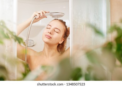 Beautiful satisfied European woman washes away shampoo from the head hair in bathroom, takes a shower and enjoys, smiling