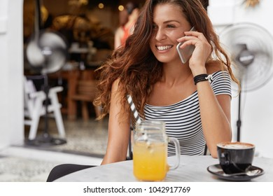 Beautiful satisfied female with cute smile, enjoys recreation time in cafeteria, calls someone via smart phone, has morning breakfast. Brunette gorgeous woman in good mood speaks on modern cellular