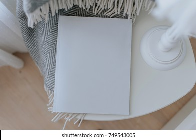 Beautiful scandinavian home decorated interior with magazine to place text on empty white cover page, on white chair, used as nightstand, with lamp and cozy grey blanket.