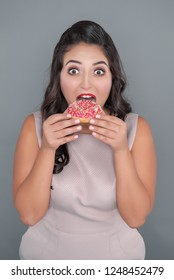 Beautiful scared plus size woman with donut. Body positive concept