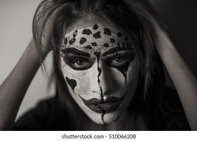 Beautiful scaring girl with mystical face art. Halloween makeup