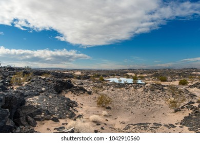 Beautiful scene of ancient lava beds along route 66 adjacent to Mojave National preserve along interstate 40 with a rain pond