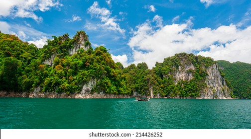 Beautiful scene of boat on green clear water with rock mountain in Ratchaprapa Dam, Suratthani, Thailand