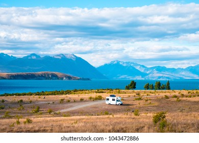 Beautiful scene of campervan, car, the yellow grassland mt cook and lake tekapo before sunset.