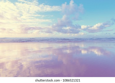 Beautiful scene cloudy blue sky reflected on beach wet sand.