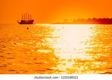 Beautiful scene with cruise sailboat sailing in sea at sunset near shore