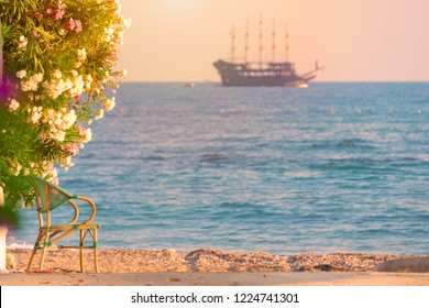Beautiful scene with cruise sailboat sailing in sea at sunset at horizon. View from beach with chair in foreground.
