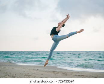 Beautiful scene of a dancing ballerina in black top and jeans on sandy beach near ocean or sea in morning. Beautiful brunette woman practicing stretching and exercises. Copy space