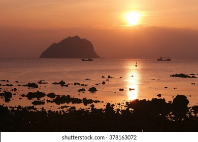 Beautiful scene of a fishing boat on the ocean and a small island in the distance as the golden sun rises over Jeju Island in South Korea.