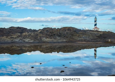 Beautiful scene fo a Lighthouse in spain under a cloudy skay with its reflection in the water of a lake