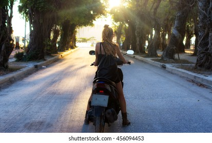 Beautiful scene with a girl sitting a motor scooter.