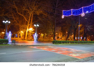 Beautiful scene of Kutaisi in a New Year night. City night park in autumn with paths strewn. Central night street