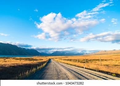 Beautiful scene of the road amoung the yellow grassland mountain and cloud beside lake tekapo before sunset.