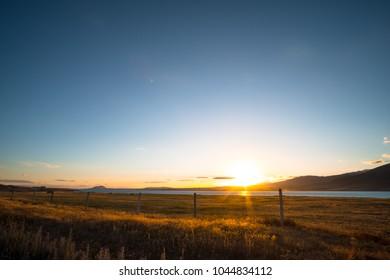 Beautiful scene of the sunset over the lake with yellow grassland at lake tekapo.