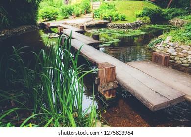 Beautiful scene of Wooden Footbridge In Japanese-Style Garden over ponds.
