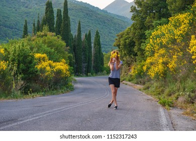beautiful scene with a young girl holding some of freshly picked wild sunflowers from the bushes of wild sunflower bloom in yellow, colorful scene