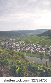 A beautiful scenery across Mosel river in Germany. Wine yards are in the high hills in the foreground and a small village in the background. Plenty of room for text. Image has a vintage effect applied