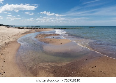 Beautiful scenery of the Baltic Sea. A beach of pure sand with small stones and clear water.