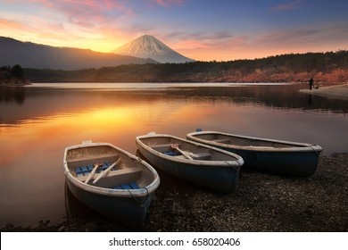 Beautiful scenery during sunrise of Lake Saiko in Japan with the rowboat parked on the waterfront and Mountain Fuji background. Travel and Attraction Concept