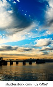 A beautiful scenery of a ferry coming into a dock against the Olympic Mountains during the sunset