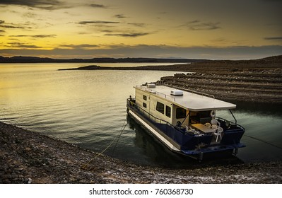 Beautiful scenery with a houseboat moored to a muddy shore in Lake Mead National Recreation Area at dusk with copy space, Nevada - vacation and holidays concept.