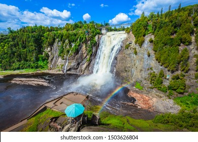 Beautiful scenery landscape view of Montmorency Falls and magnificent rainbow against mountain, bridge, blue sky, clouds in Montmorency Falls Park, Quebec, Canada. Large waterfall on Montmorency River