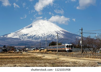 Beautiful scenery of a local train traveling through harvested farmlands with the majestic snow capped Mount Fuji in background under blue clear sky on a sunny winter day, in Gotenba, Shizuoka, Japan