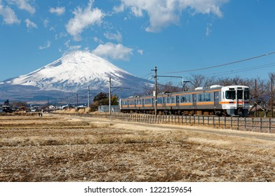 Beautiful scenery of a local train traveling through harvested farmlands with the majestic snow capped Mount Fuji in background under blue clear sky on a sunny winter day, in Gotemba, Shizuoka, Japan