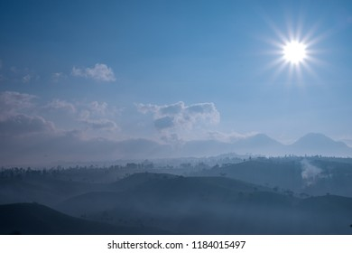 Beautiful scenery of misty morning in tea plantation under sun light and blue sky, Bandung, Indonesia