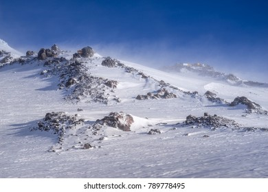 Beautiful scenery mountain massif on North Caucasus on winter resort. Old house on top of the ridge and strong winds with blizzard