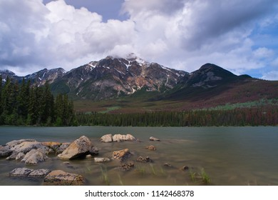 Beautiful scenery in the mountains. A lake with rocks in front. Wonderful clouds and colors.