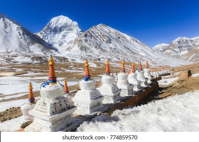 Beautiful scenery North face of sacred Kailash mountain covered with snow with group of white tibetan chortens(pagoda) in foreground and clear blue sky in background,China